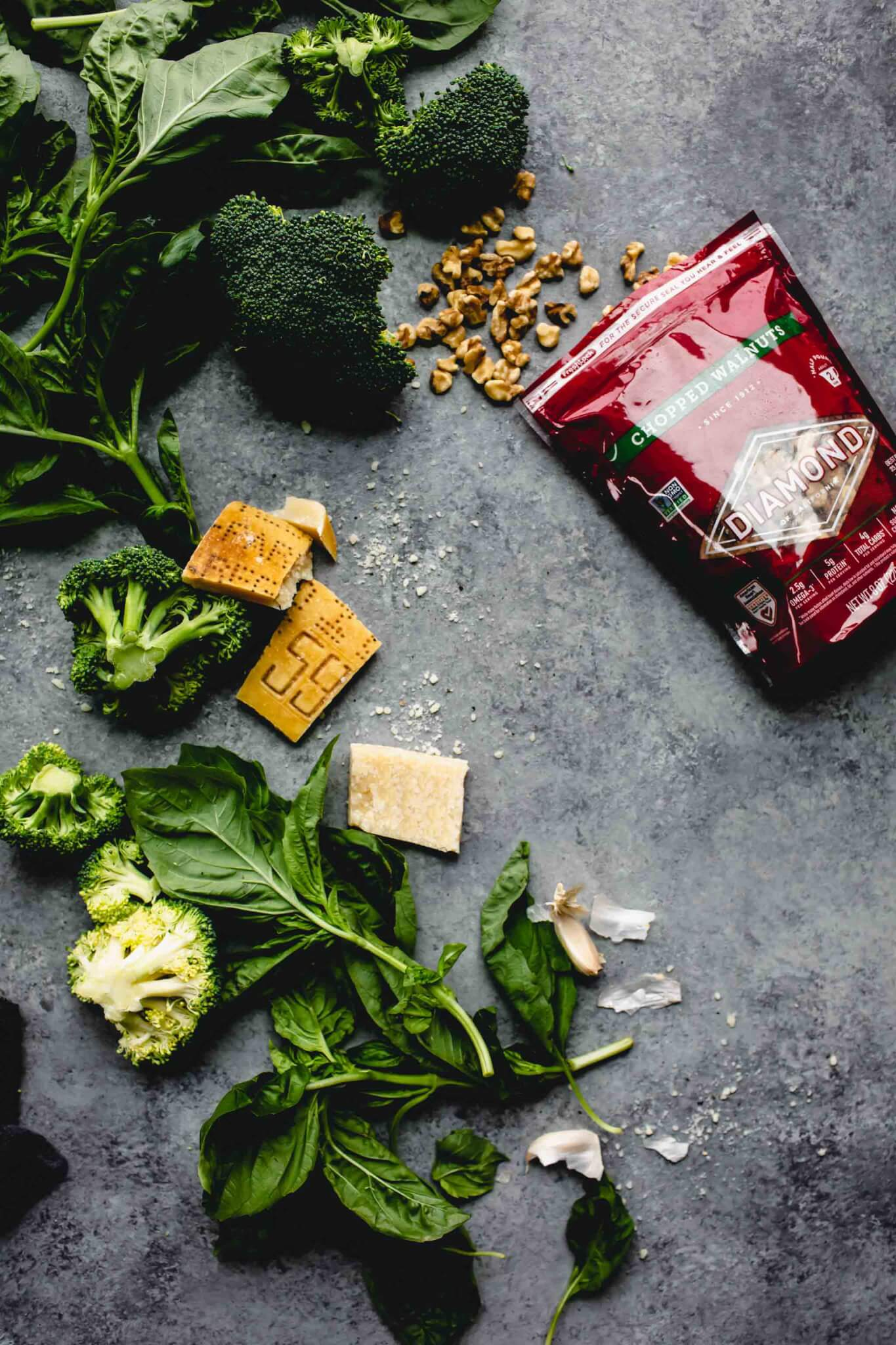 Ingredients for broccoli pesto laid out on concrete background.