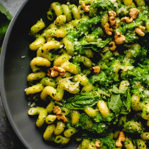 Overhead close up of bowl of pasta tossed with broccoli pesto.