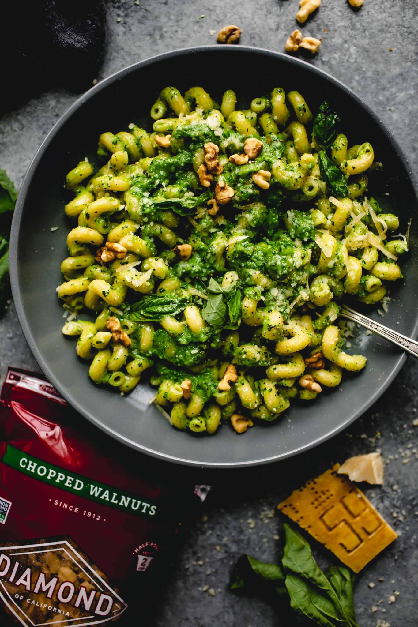 Bowl of cavatappi pasta tossed with broccoli pesto next to wedge of parmesan and package of walnuts.