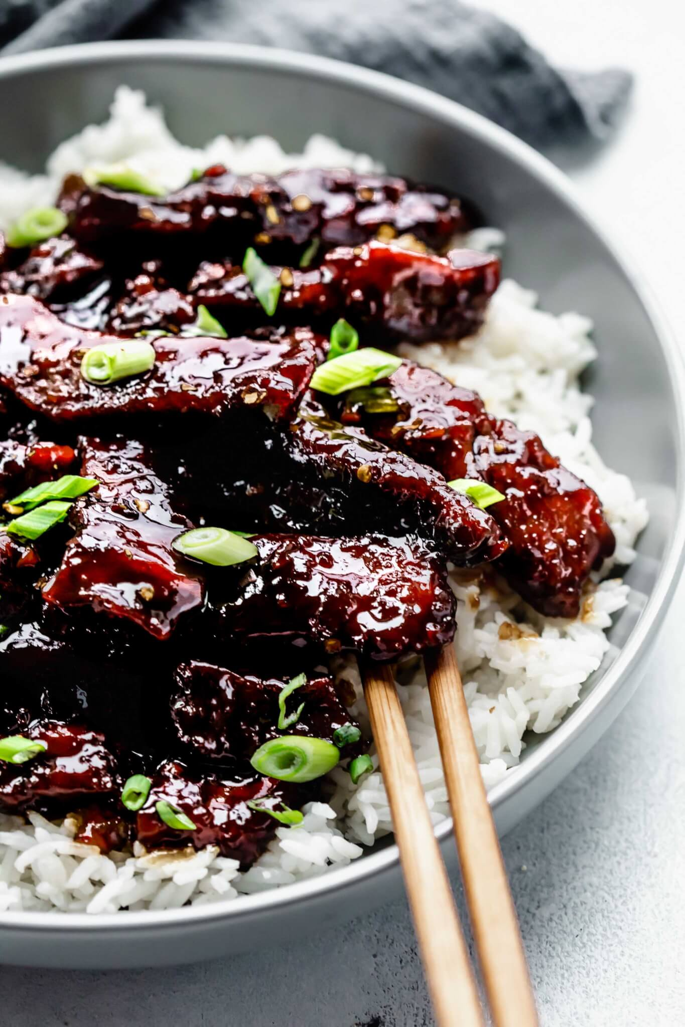 Side view of mongolian beef served on top of rice in grey bowl with chopsticks.