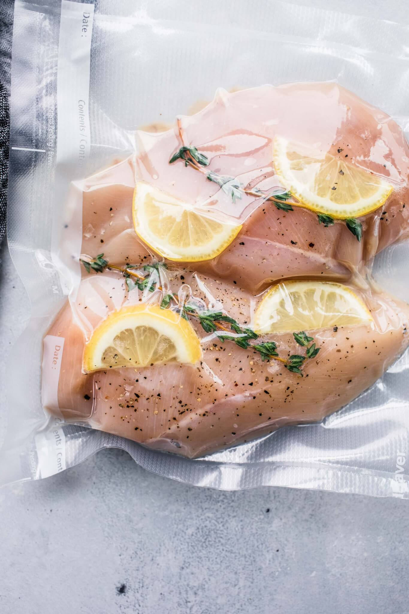Two chicken breasts in vacuum seal bag with lemons and herbs.