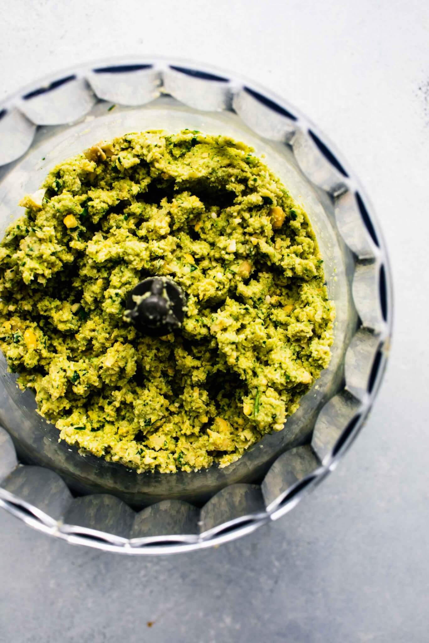 Processed falafel mixture in food processor bowl.