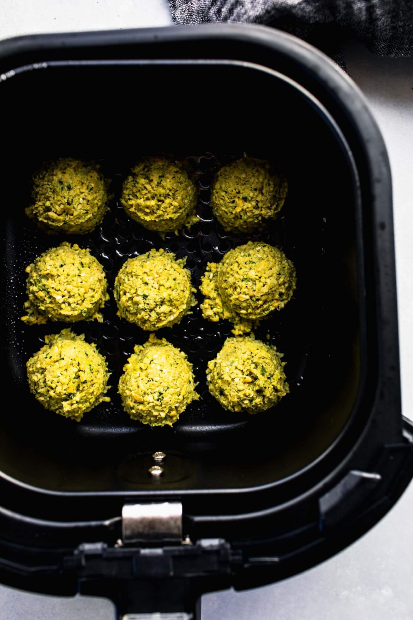 Uncooked falafel balls in air fryer basket.