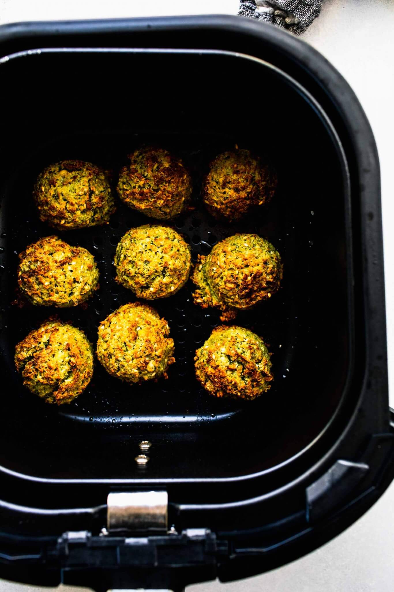 Cooked falafel in air fryer basket.