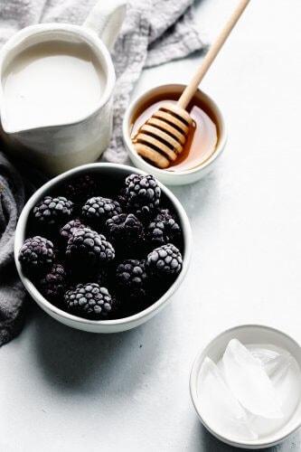 Bowl of frozen blackberries next to honey wand.