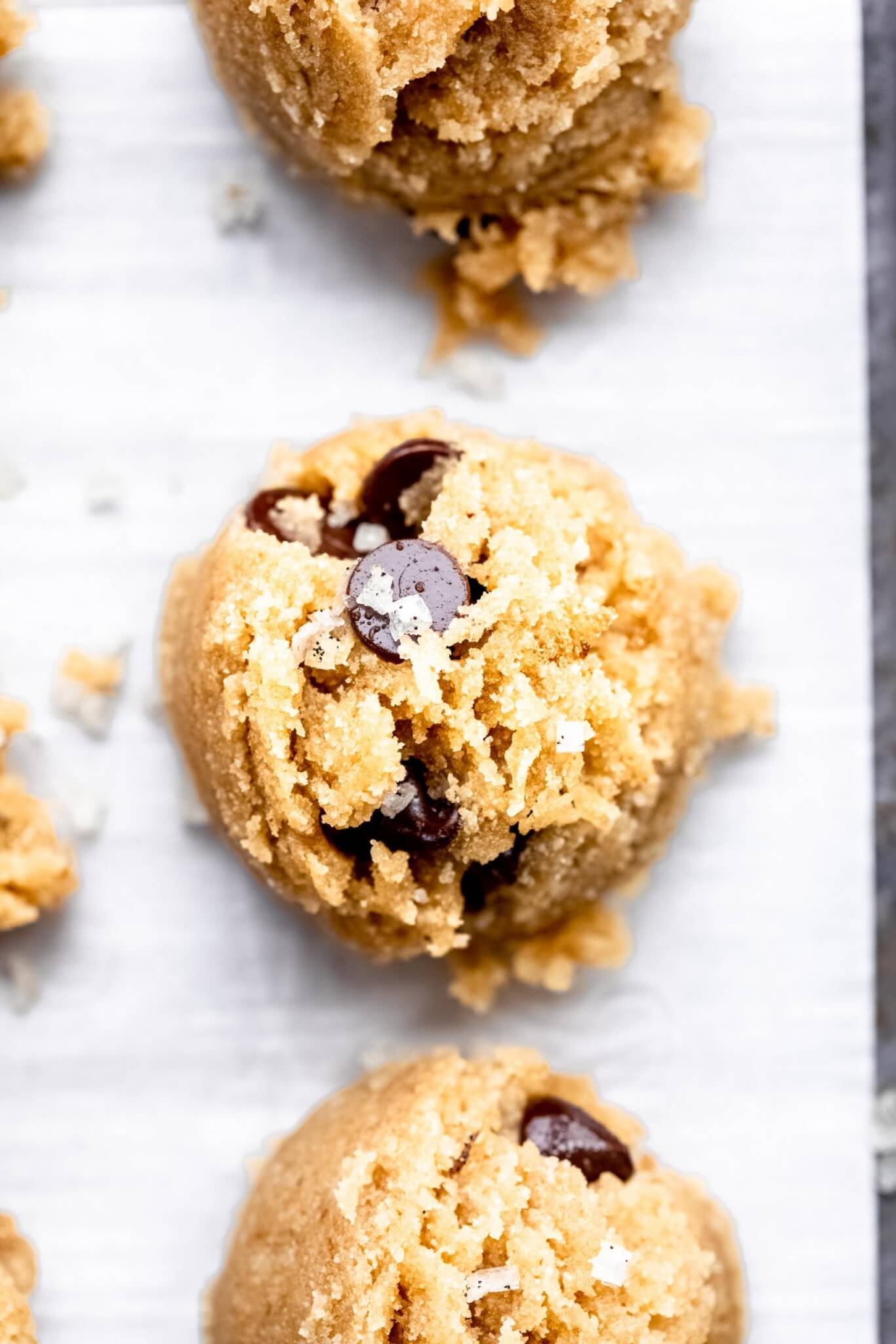 Overhead close up of cookie dough bites on parchment lined baking sheet.