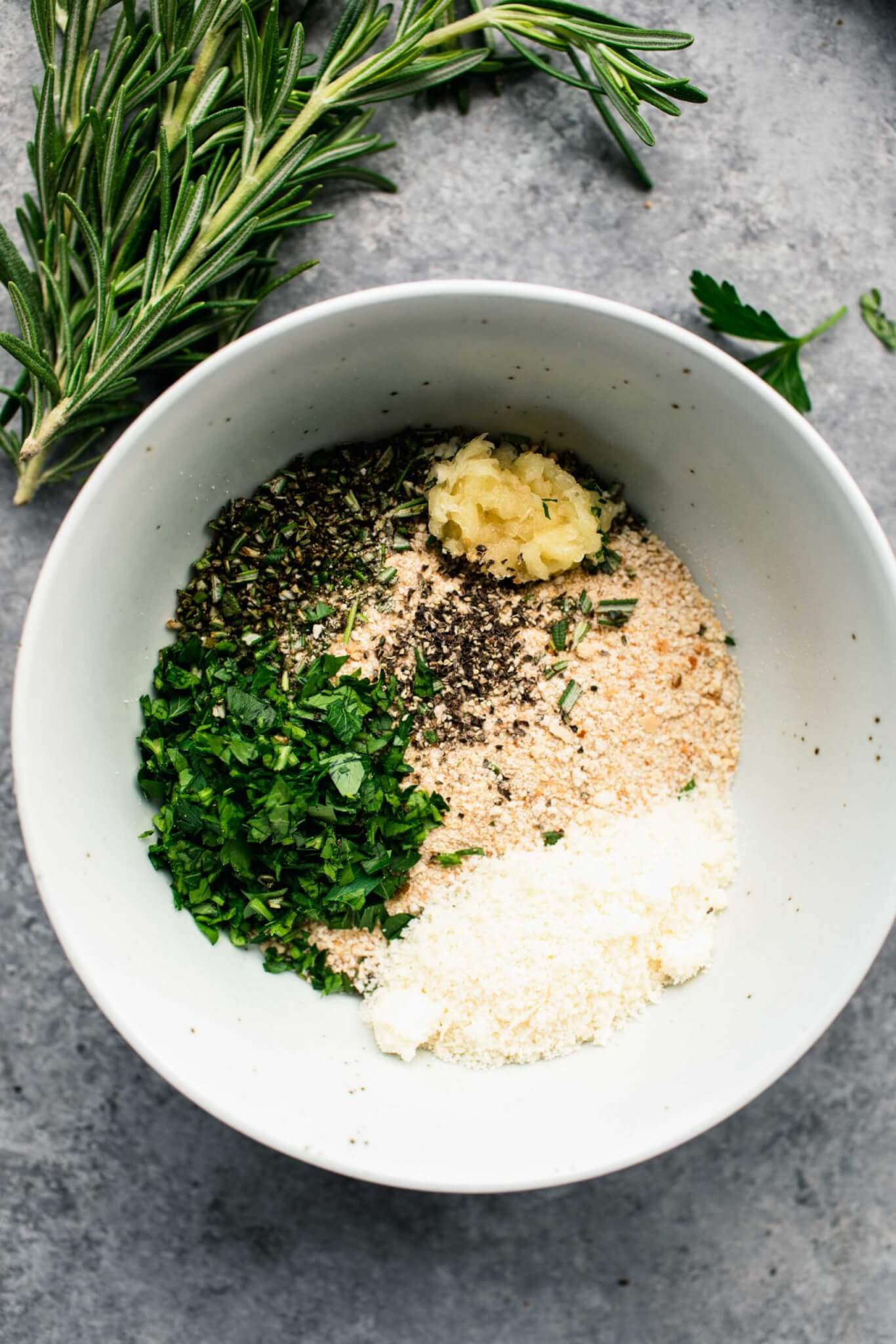 Breadcrumbs, herbs and parmesan cheese in small white bowl.