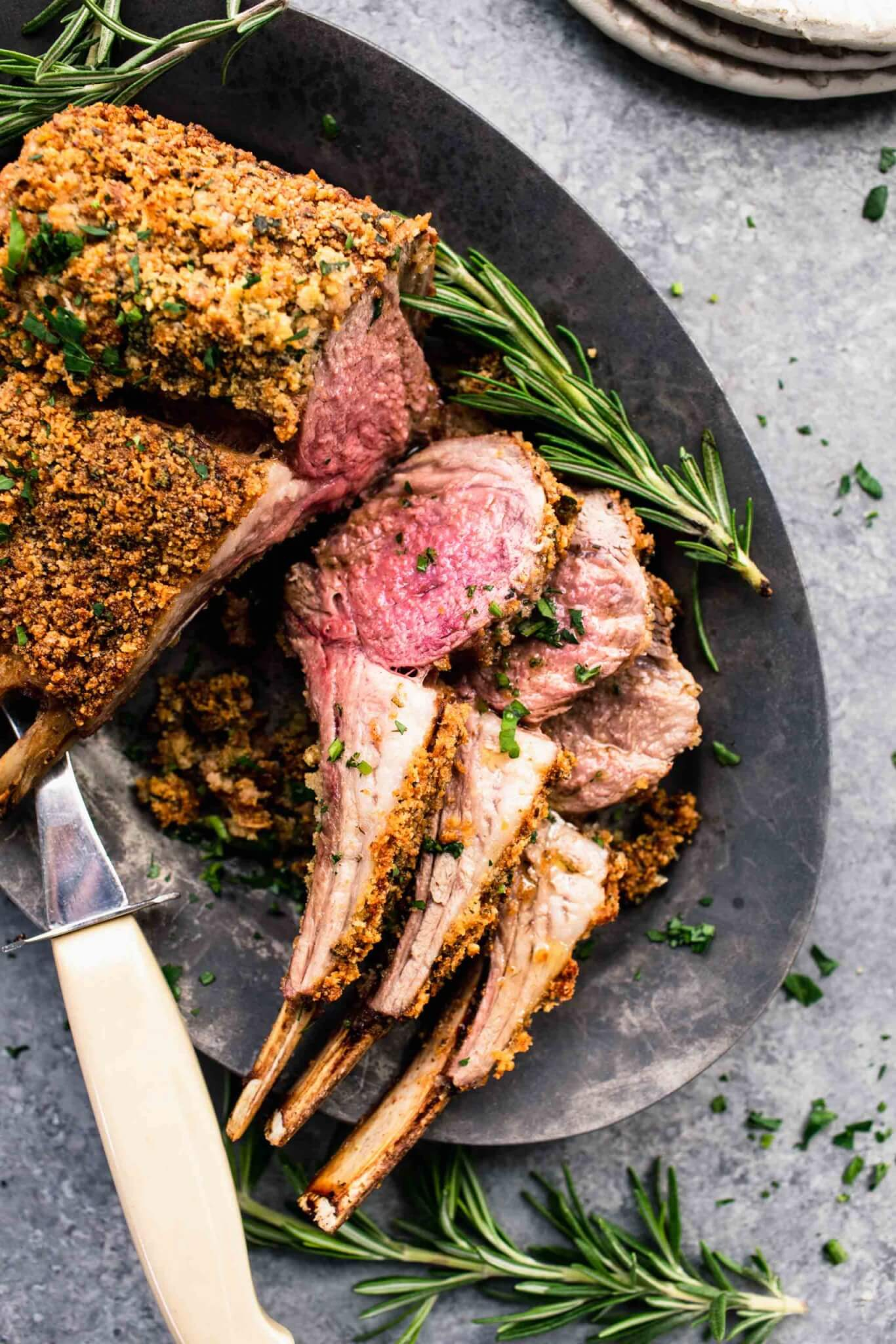 Herb crusted rack of lamb on grey serving platter with three chops sliced off.