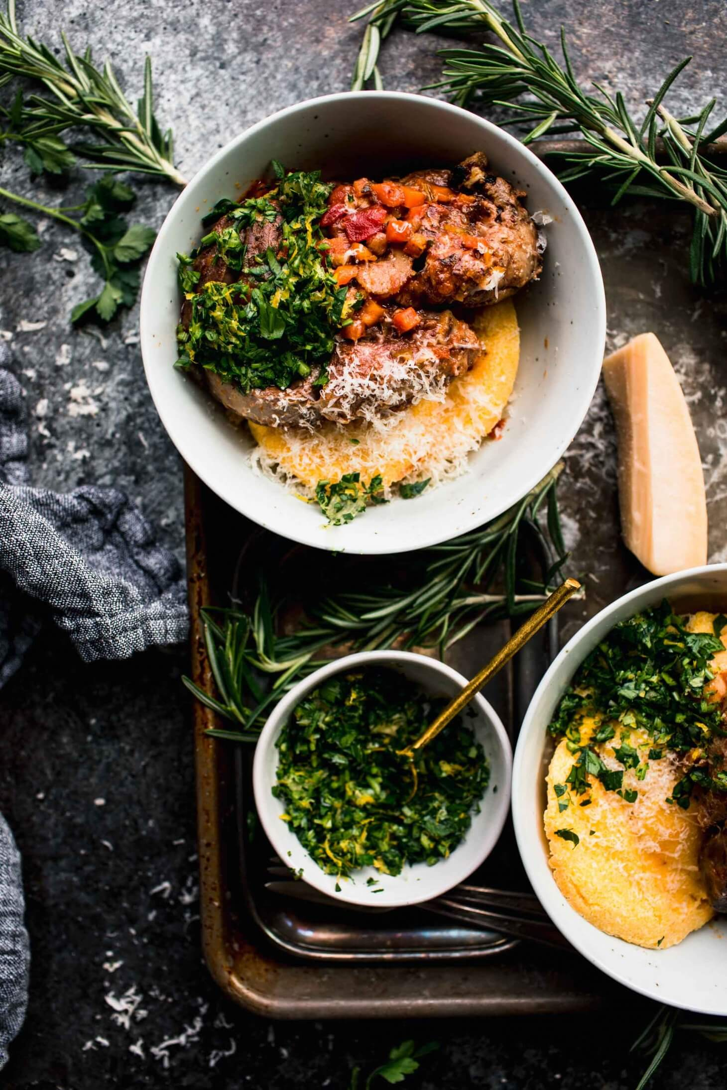 Two bowls of prepared osso buco on top of polenta on serving tray next to sprigs of fresh herbs and bowl of gremolata.
