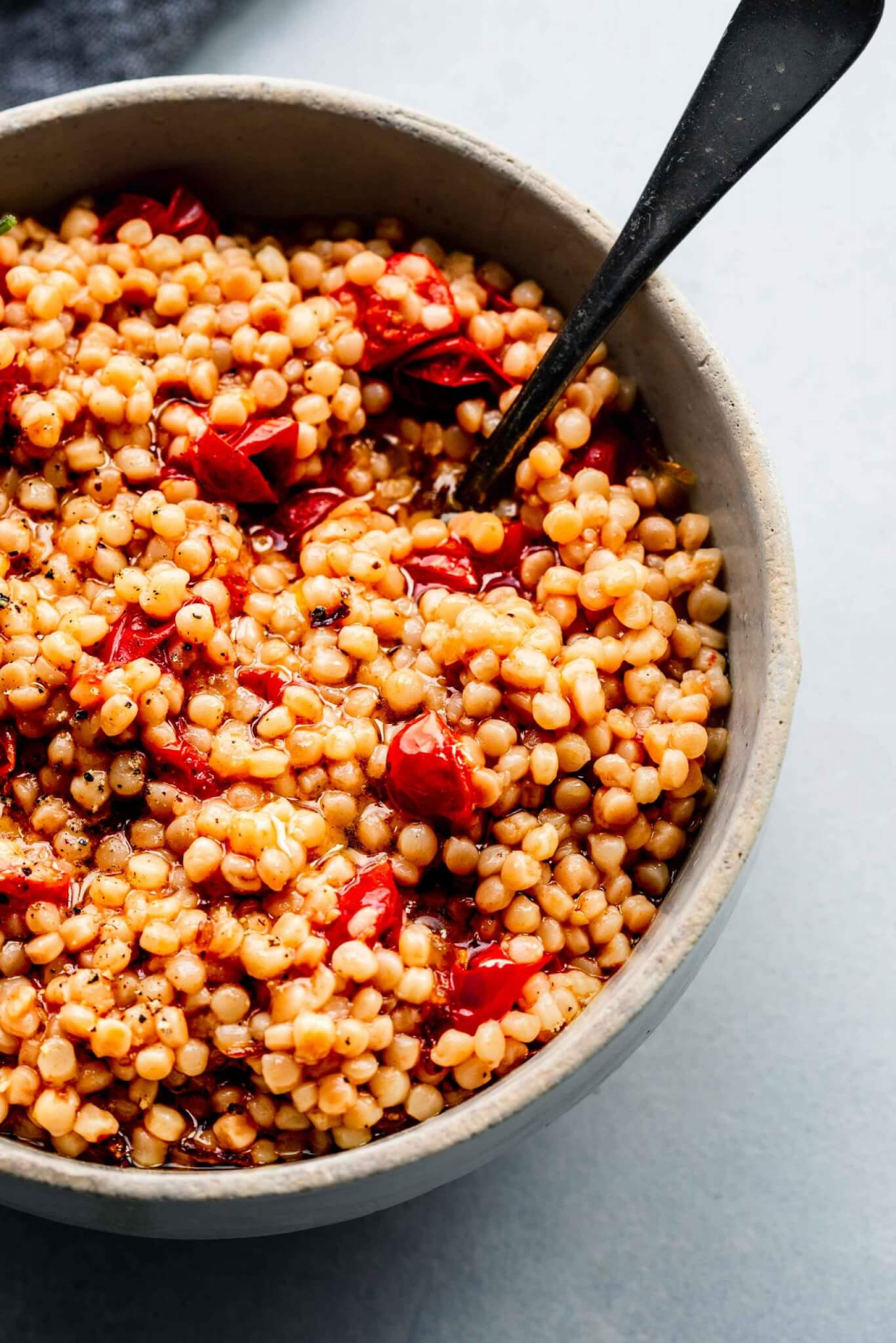 Side view of bowl of cooked tomato couscous with spoon.