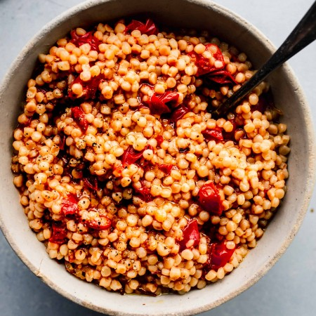 Overhead shot of bowl of cooked tomato couscous with spoon.