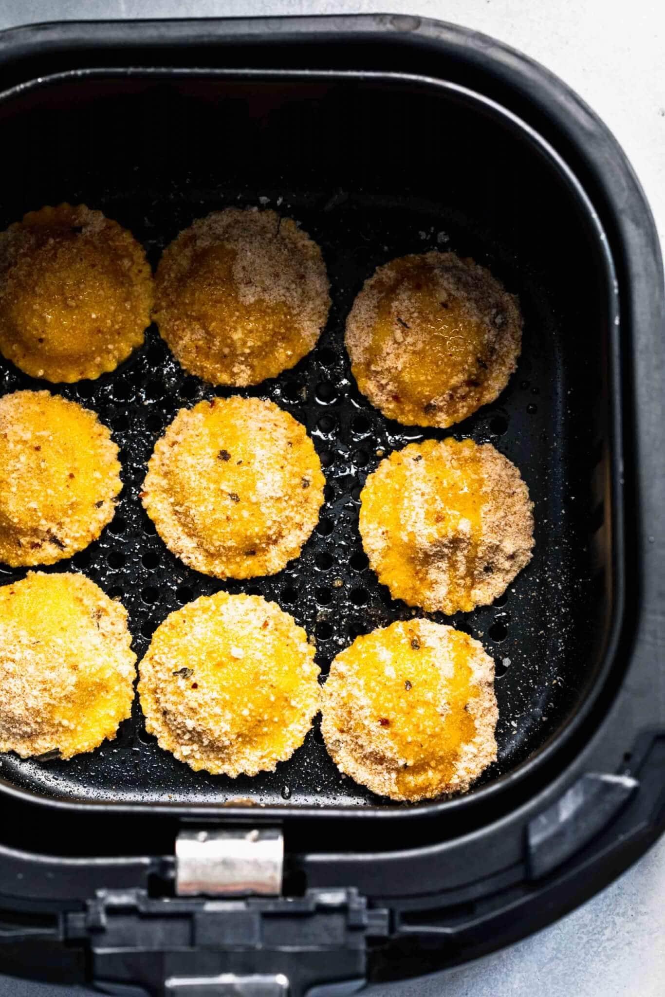Breaded ravioli in air fryer basket.