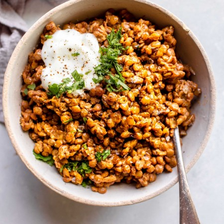 Instant pot lentils in bowl topped with yogurt and cilantro