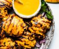 Plate of grilled mango chicken with bowl of mango sauce and charred limes.