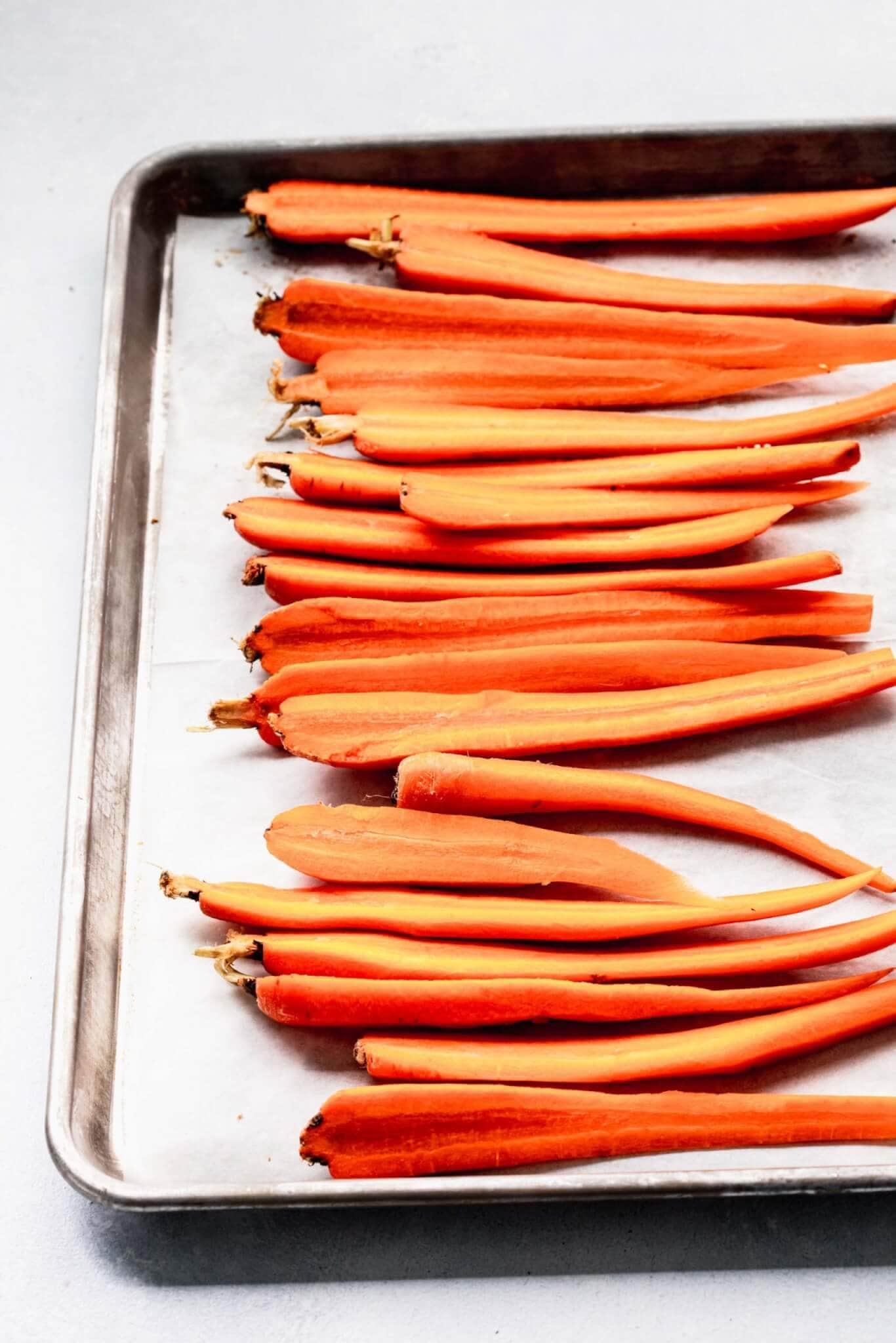 Halved carrots on baking sheet before roasting.