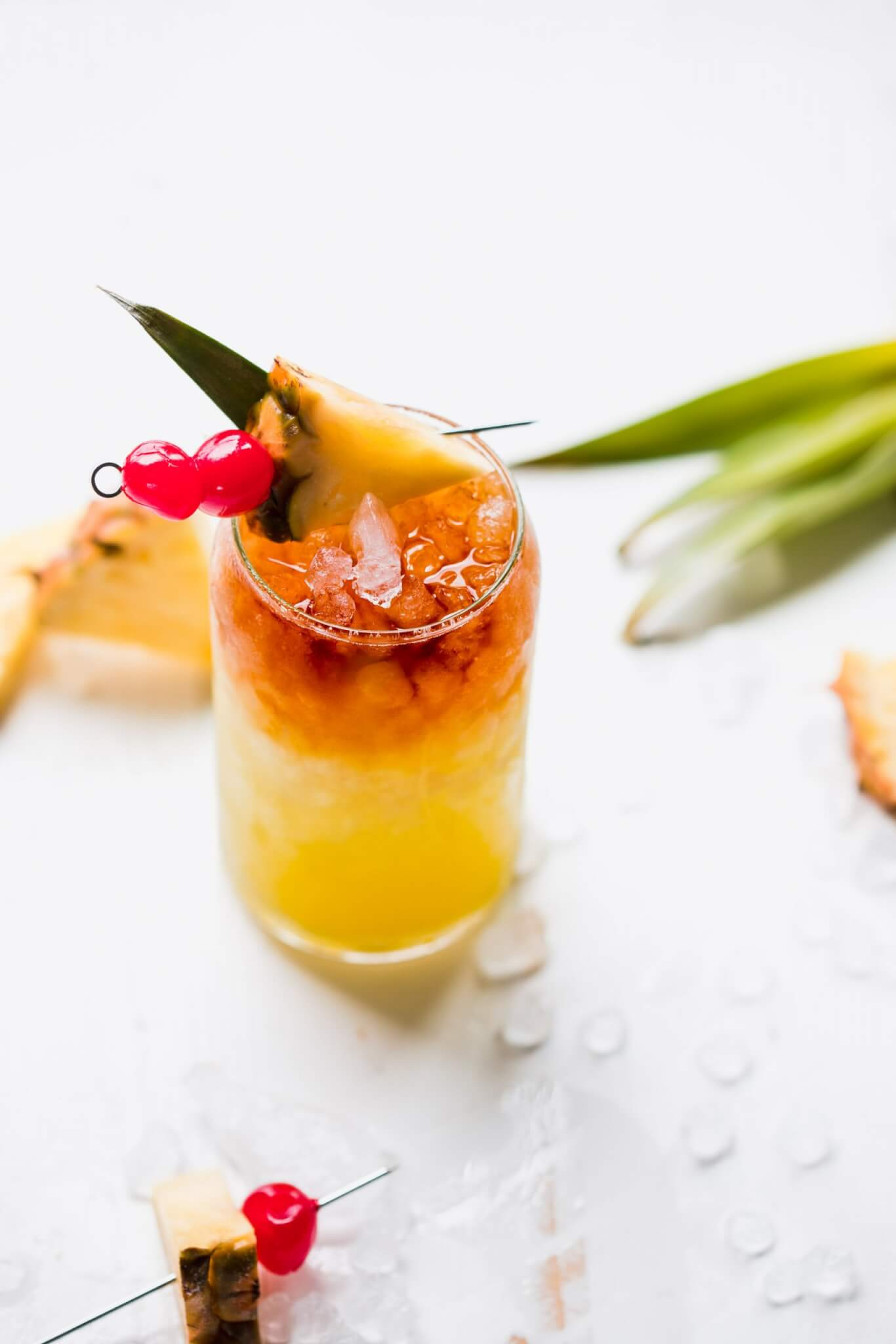 Mai tai in glass garnished with pineapple wedge and cherries.