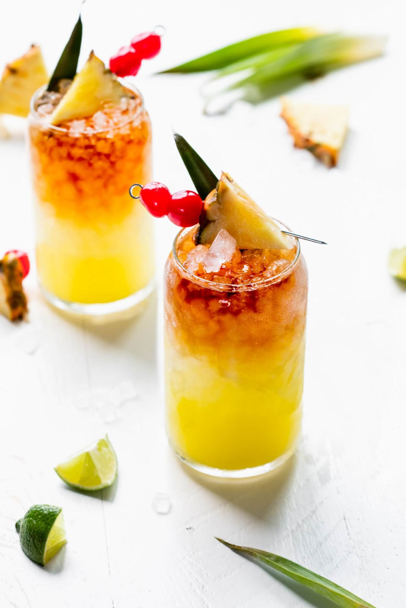 Two Mai tai cocktails in glass garnished with pineapple wedge and cherries.