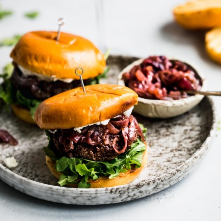 Side view of two lamb burgers arranged on plate next to bowl of caramelized onions and glass of red wine.