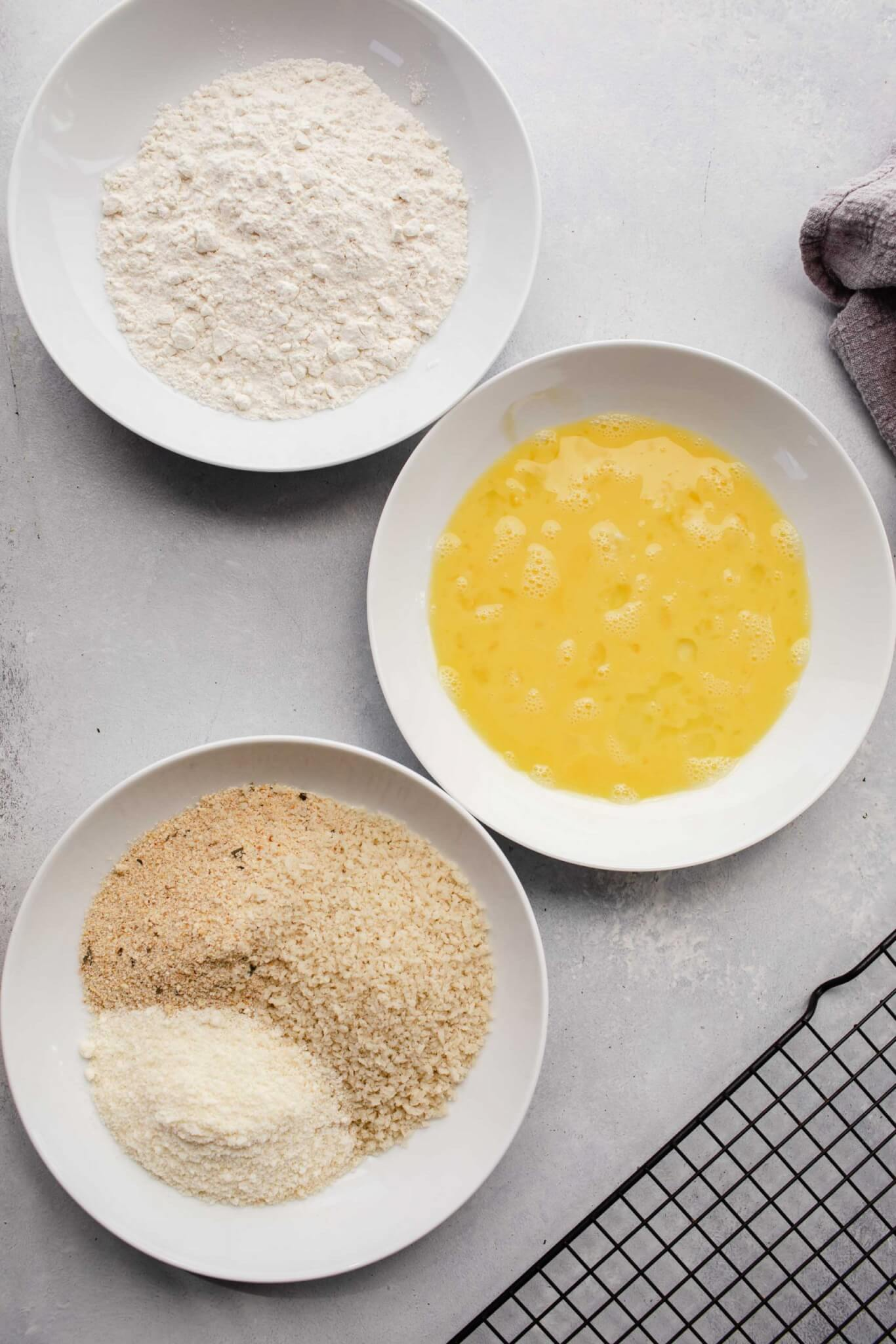 Three bowls with flour, eggs and breadcrumbs.