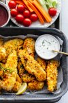 Air fried chicken strips on a tray next to ranch dressing and plate of vegetables.