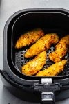 Chicken strips in air fryer basket.