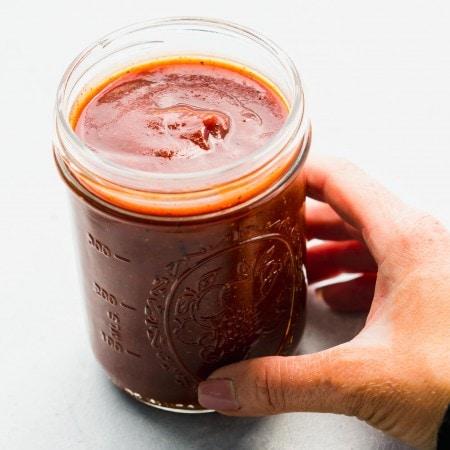 Hand holding jar of homemade bbq sauce