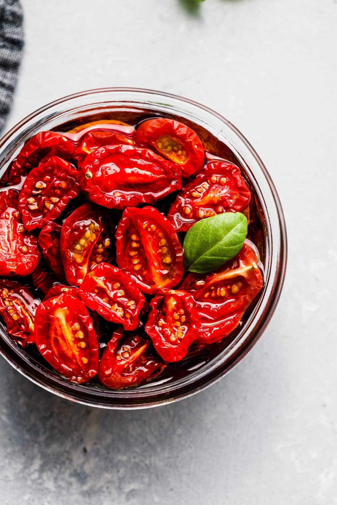 Overhead shot of sun dried tomatoes in jar with olive oil and basil.