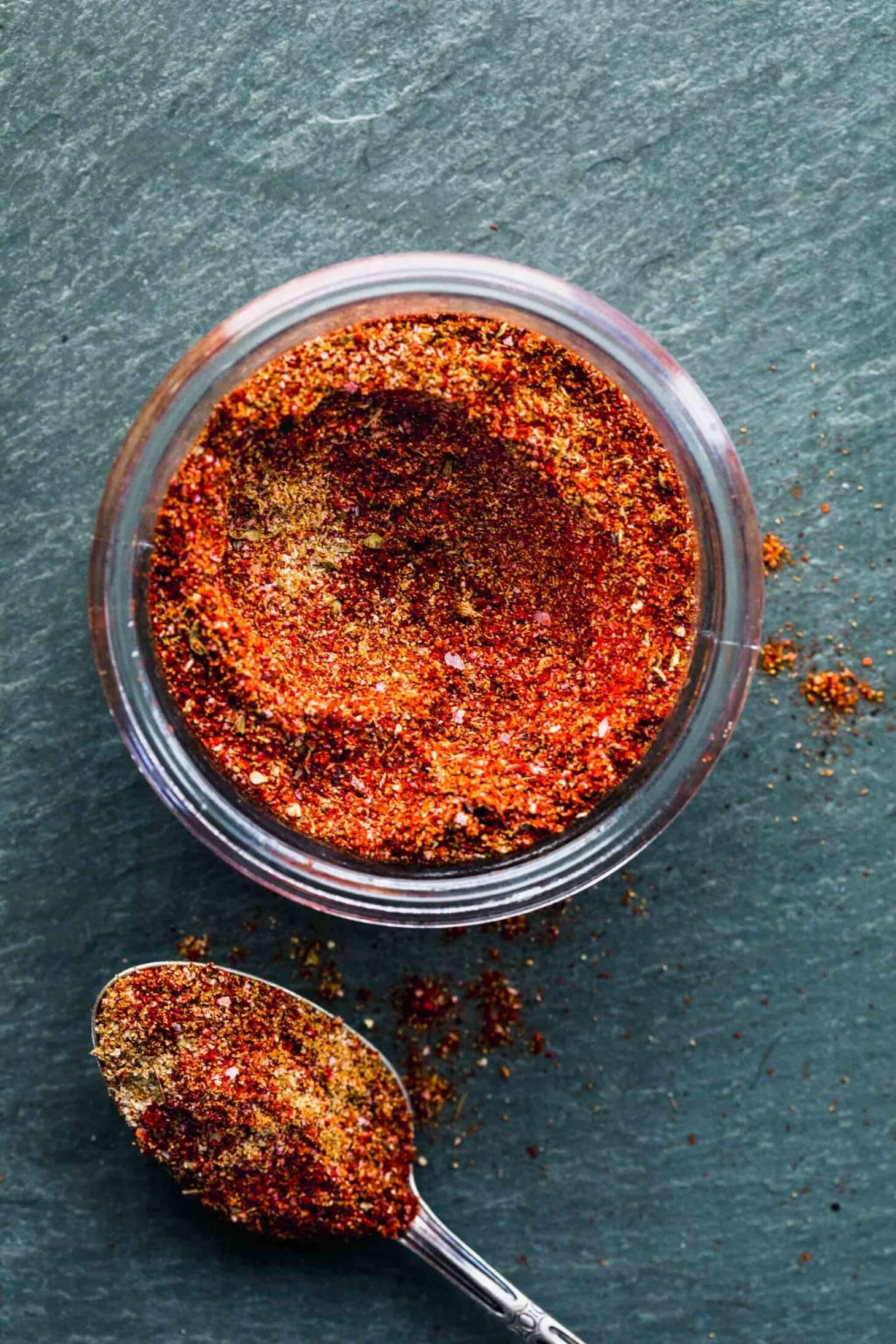 OVERHEAD SHOT OF TACO SEASONING IN GLASS CONTAINER WITH SPOON NEXT TO IT