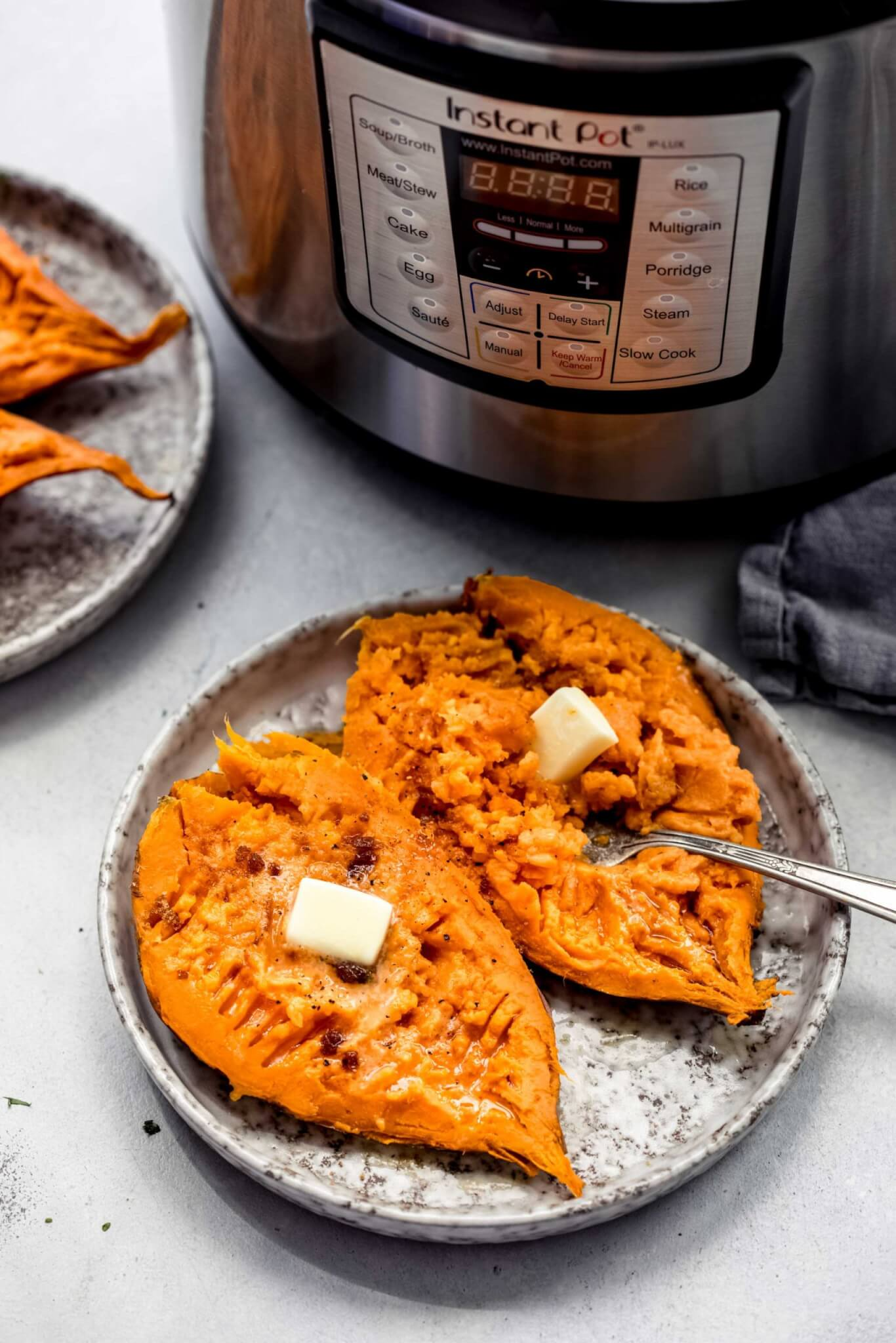 Split open sweet potato on grey plate with pats of butter and fork next to instant pot.