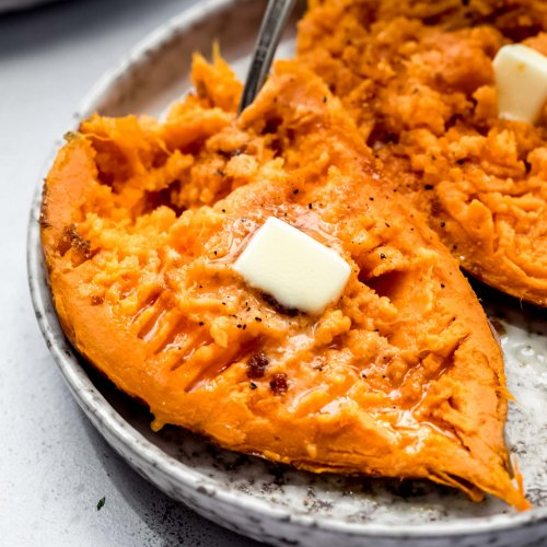 Split open sweet potato on grey plate with pats of butter and fork.