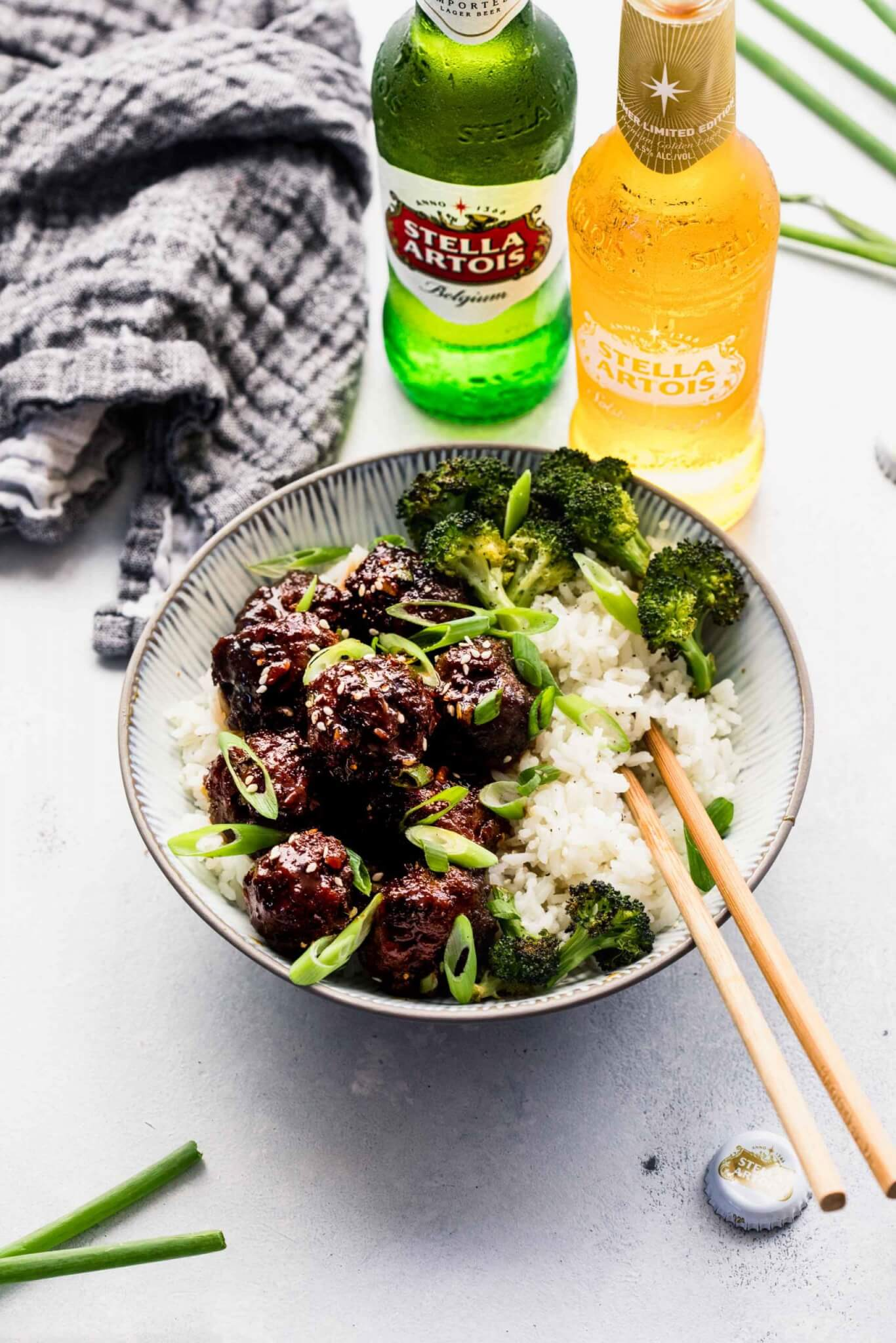 Side view of mongolian beef meatballs in grey bowl with rice, broccoli and chopsticks