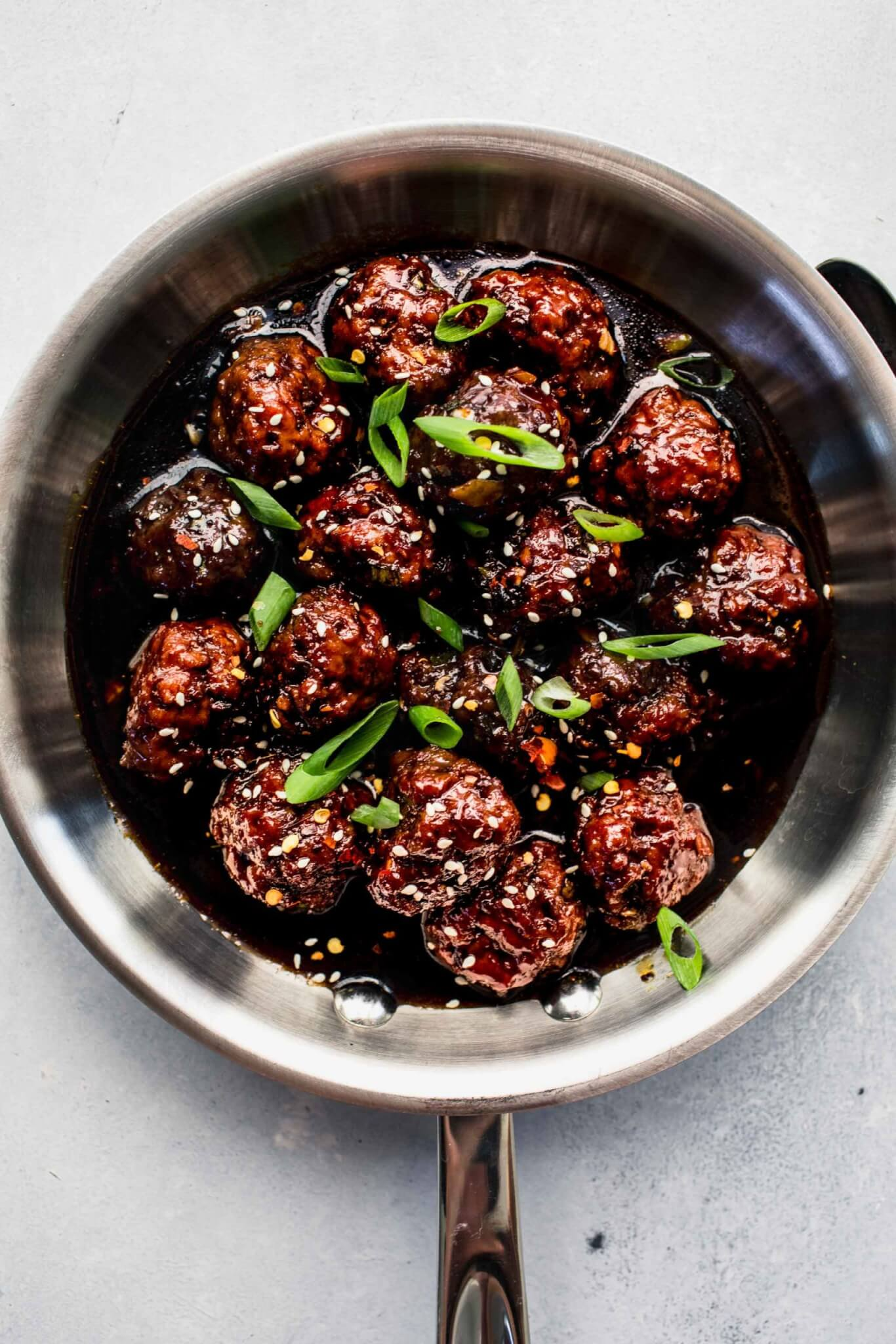 Mongolian beef meatballs in skillet with sauce.