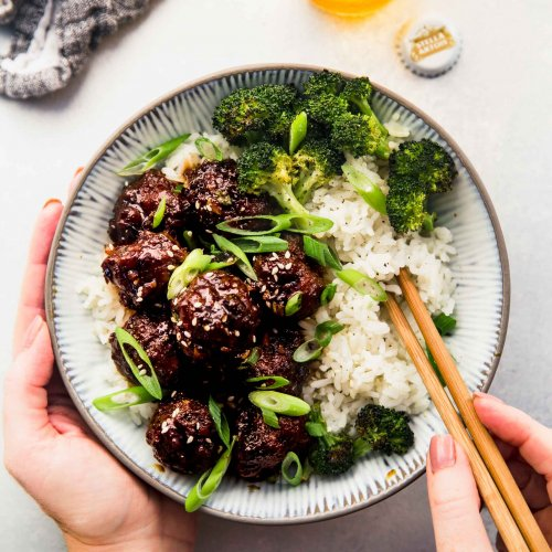Two hands holding bowl of mongolian beef meatballs and chopsticks