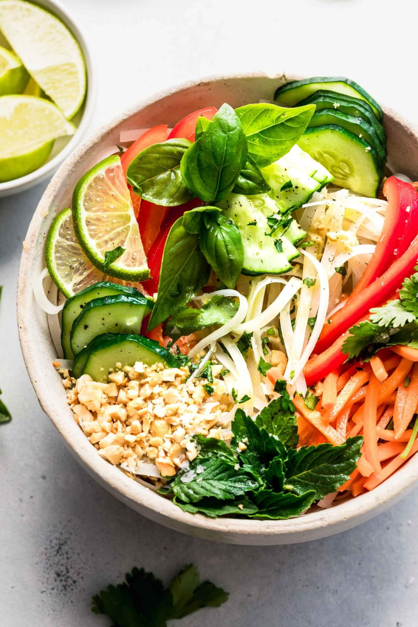 Vietnamese noodle salad in white bowl topped with chopped nuts and lime wedges.