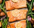 Salmon on baking sheet with green beans, potatoes and lemon slices.