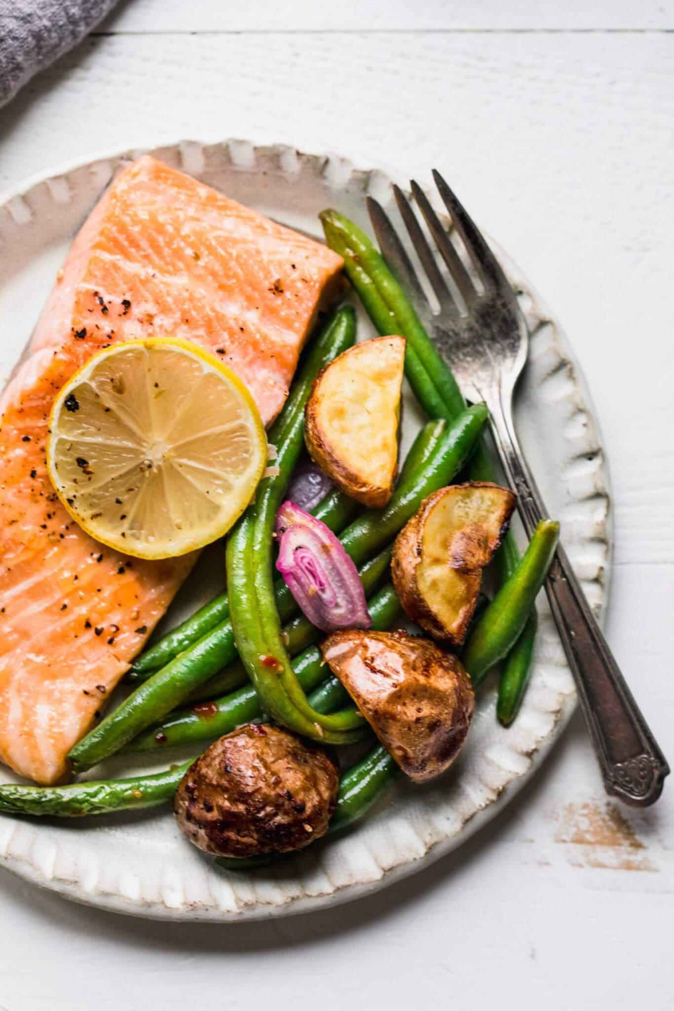 Salmon on plate with lemon slice, green beans and potatoes.