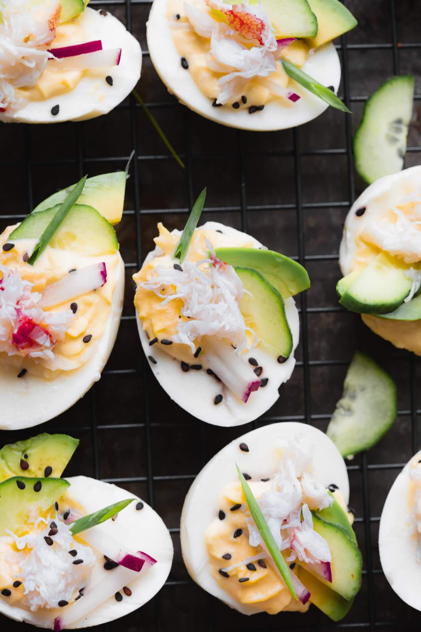 Stuffed crab deviled eggs on dark background topped with sesame seeds, avocado, radishes and cucumber.
