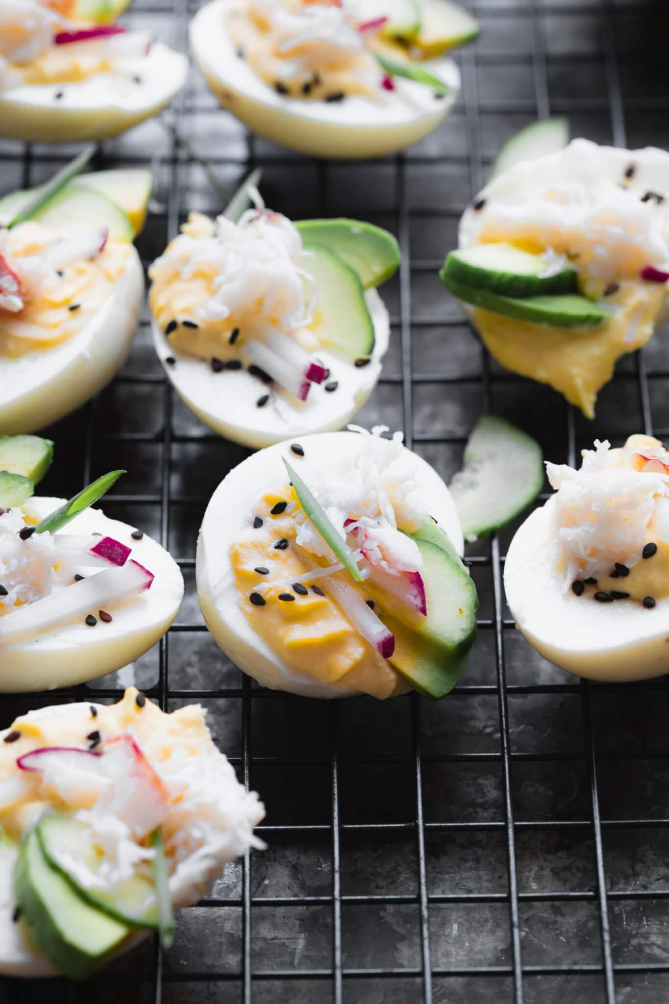 Side view of stuffed crab deviled eggs on dark background topped with sesame seeds, avocado, radishes and cucumber.