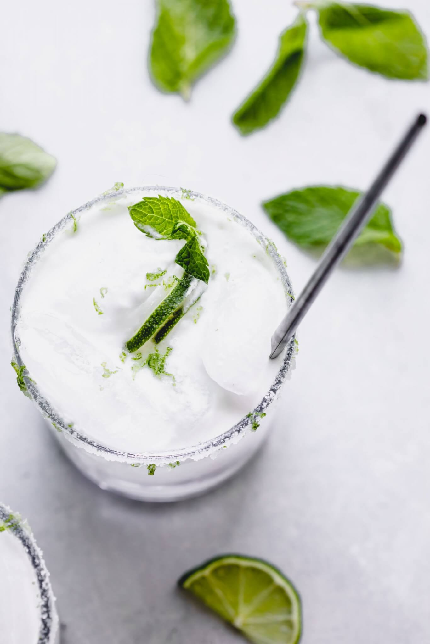 Overhead shot of coconut mojito in glass with lime slices and mint sprigs.