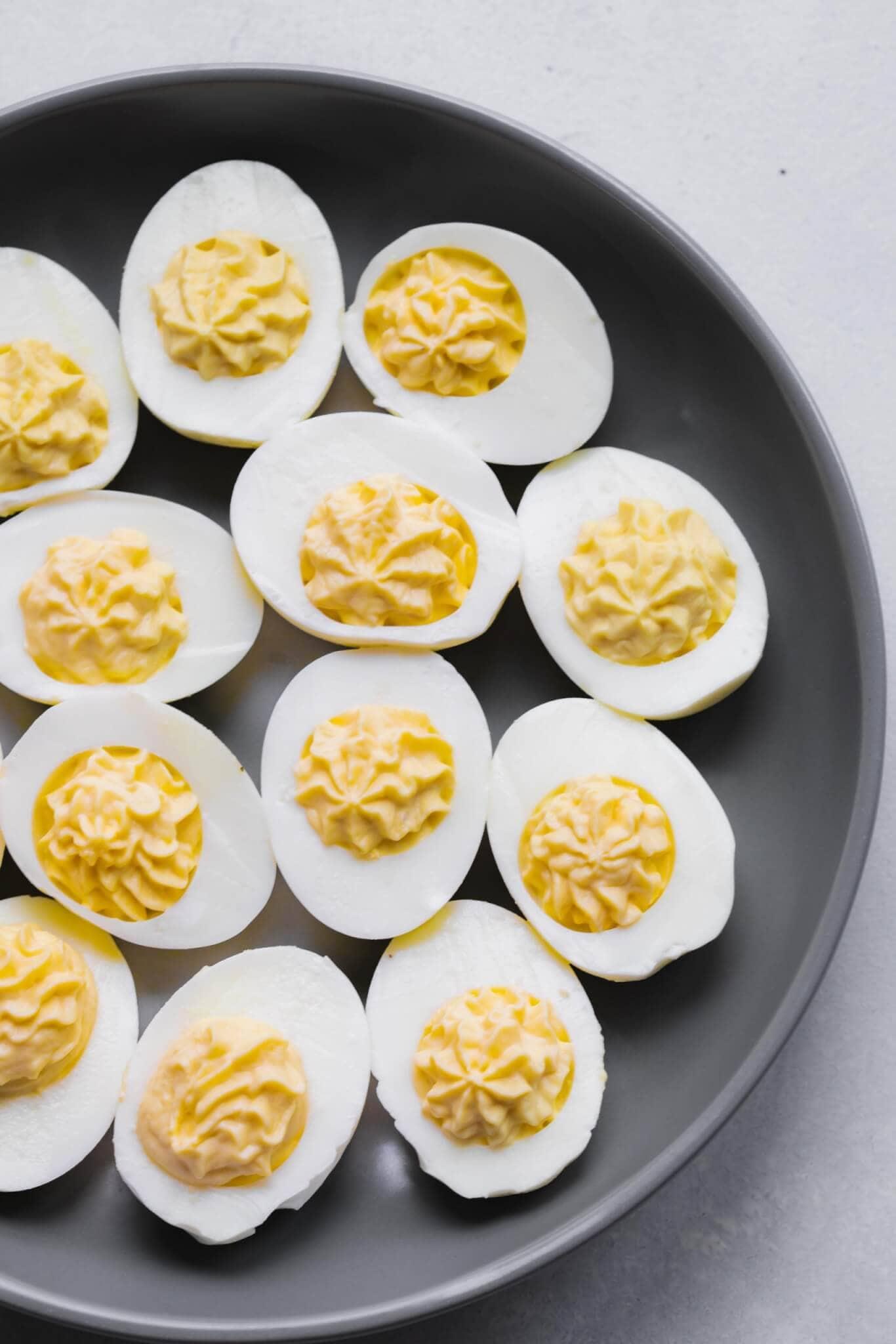Deviled eggs on grey plate before garnishing.