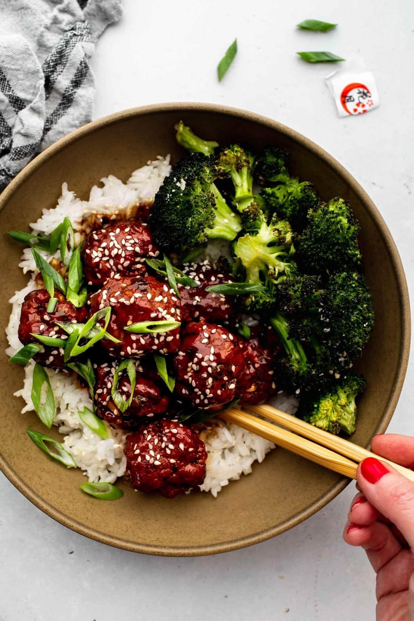 Hand holding chopsticks eating bowl of mongolian meatballs.
