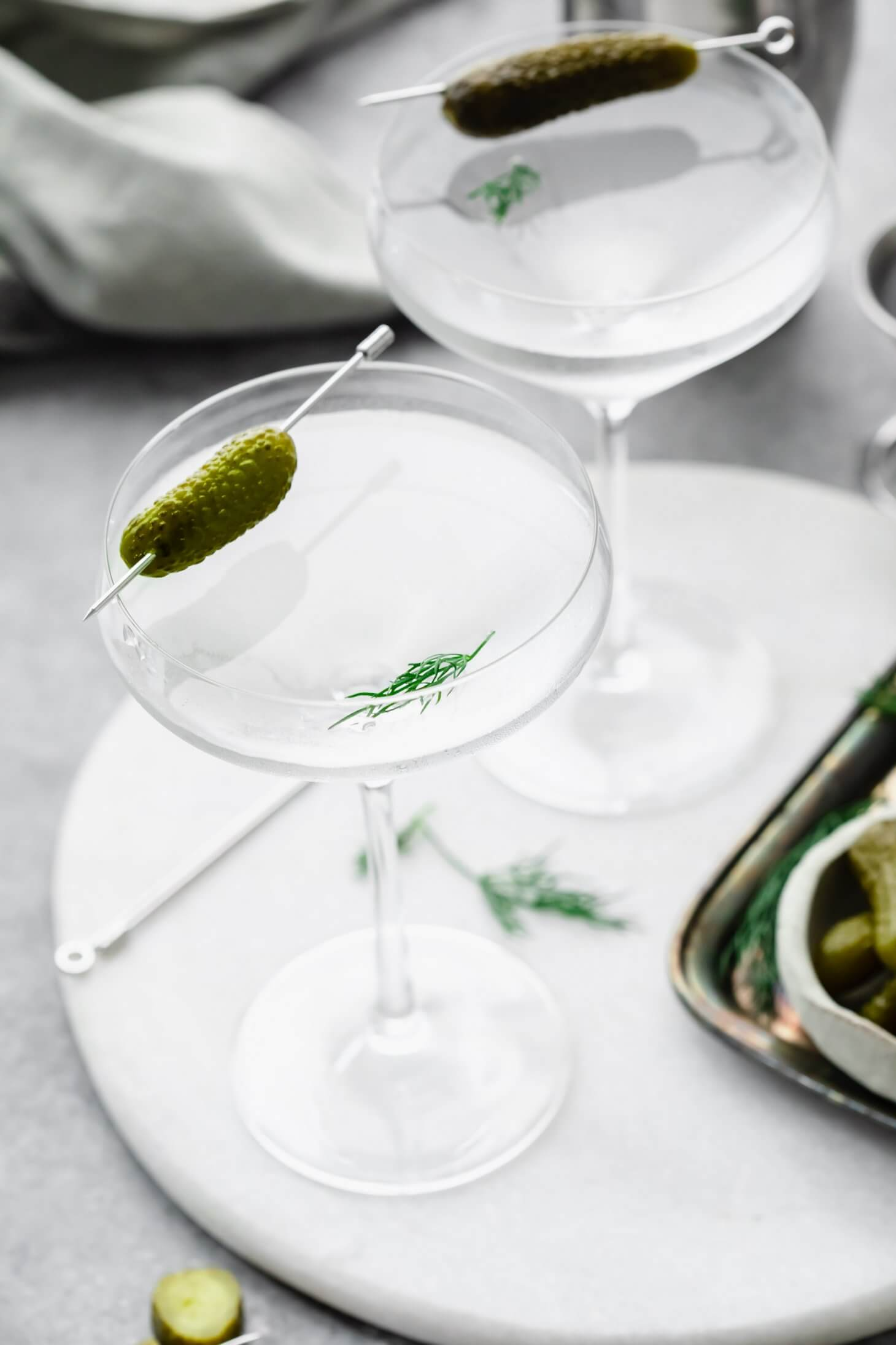 Side view of two pickle martinis garnished with small pickles.