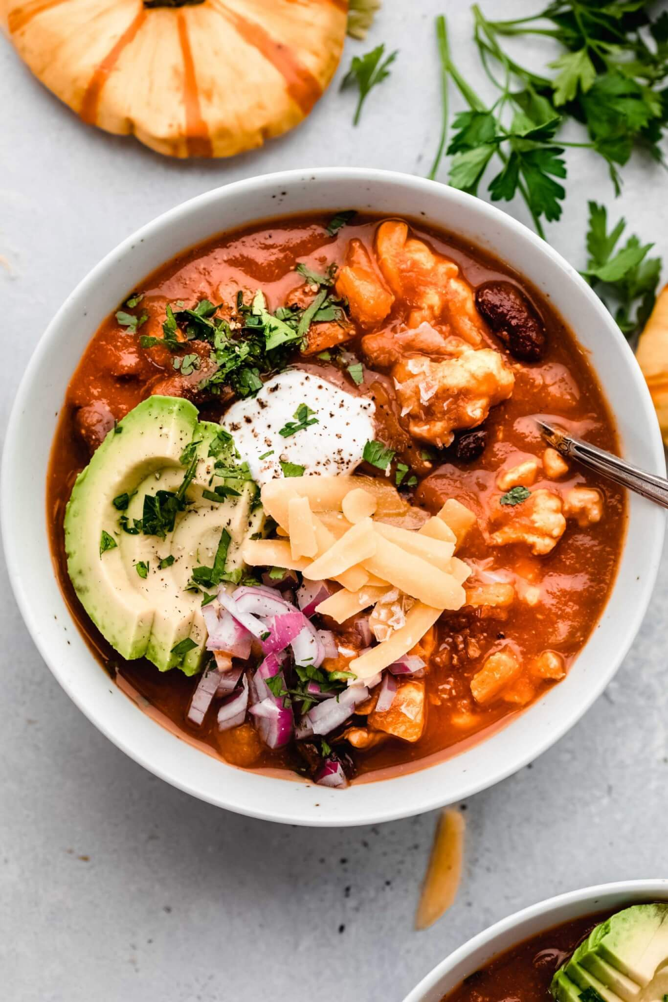 Bowl of pumpkin chili topped with cheese, avocado, sour cream and red onions.