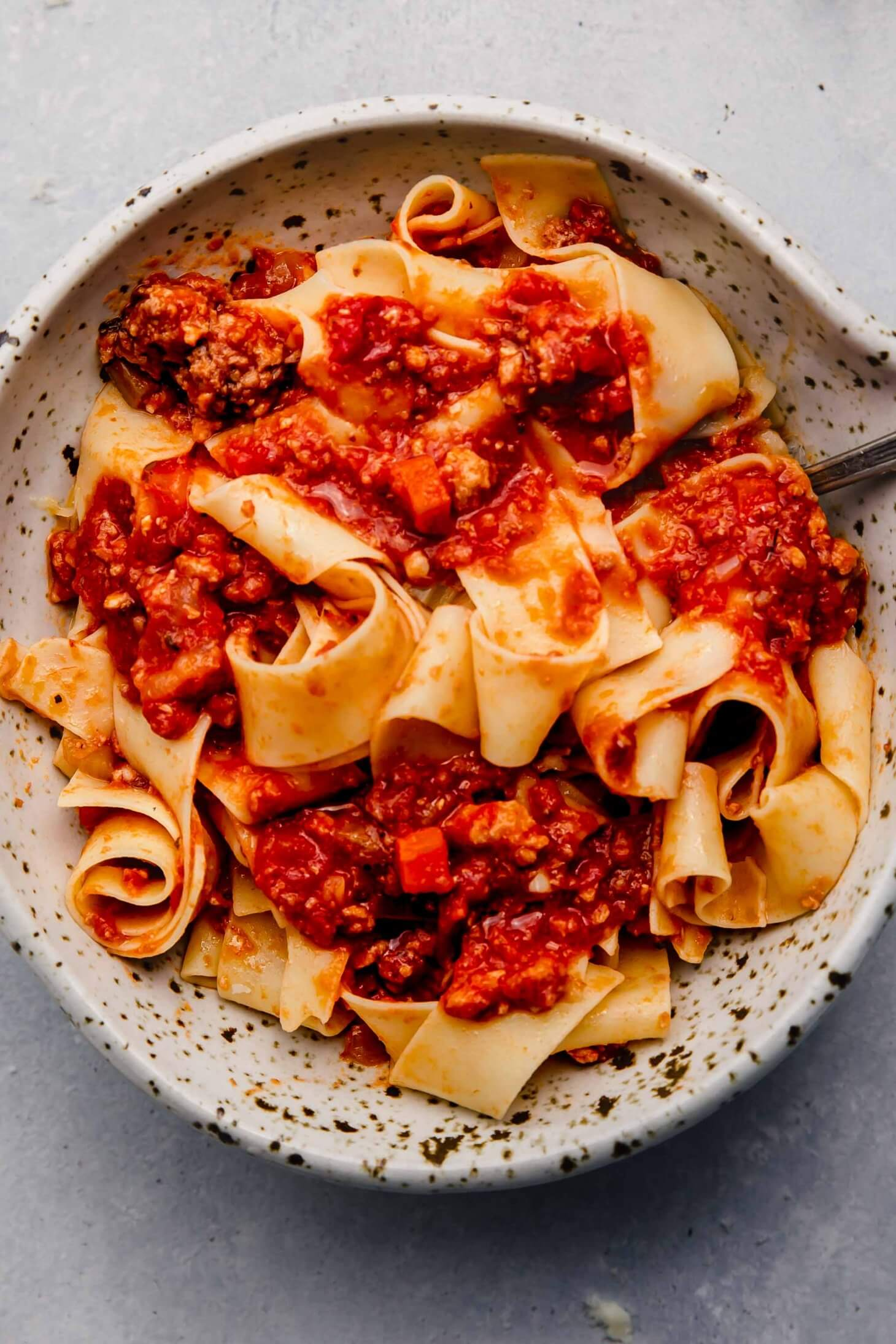 Overhead close up of bowl of pasta topped with slow cooker bolognese