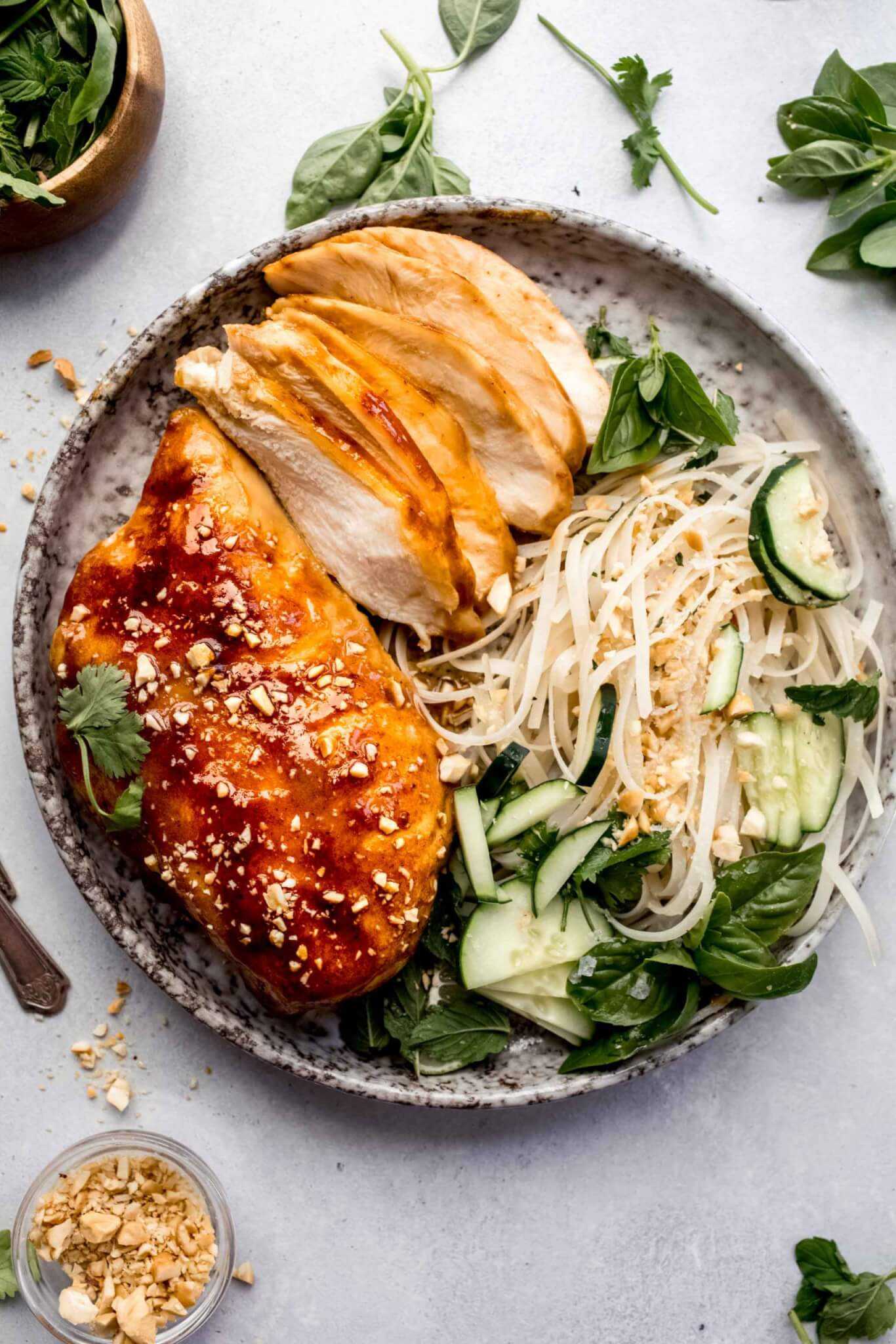 Whole sous vide miso chicken breast and sliced up miso chicken on plate with noodle salad.