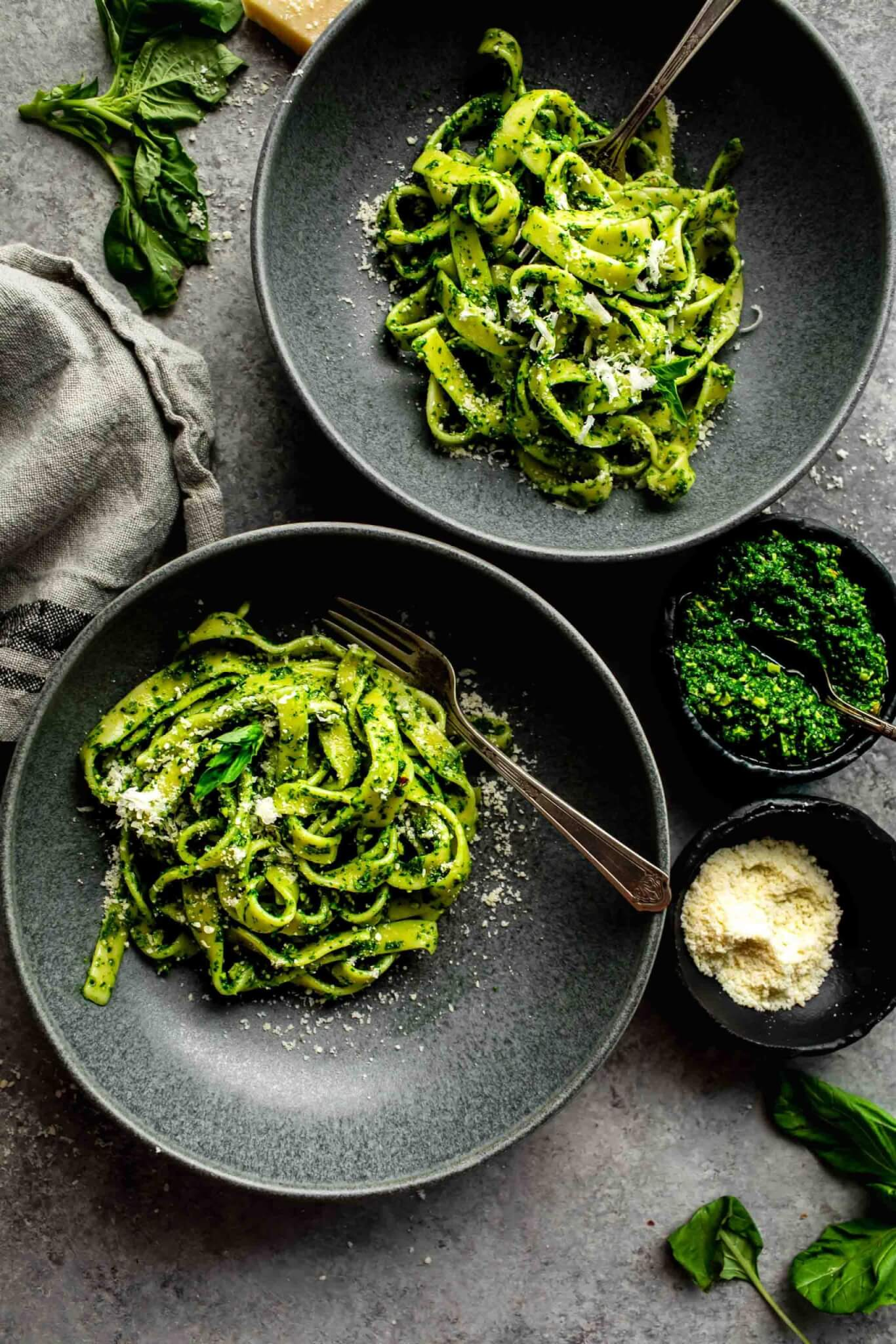 TWO BOWLS OF PASTA TOSSED WITH PESTO, NEXT TO SMALL BOWLS OF CHEESE AND PESTO