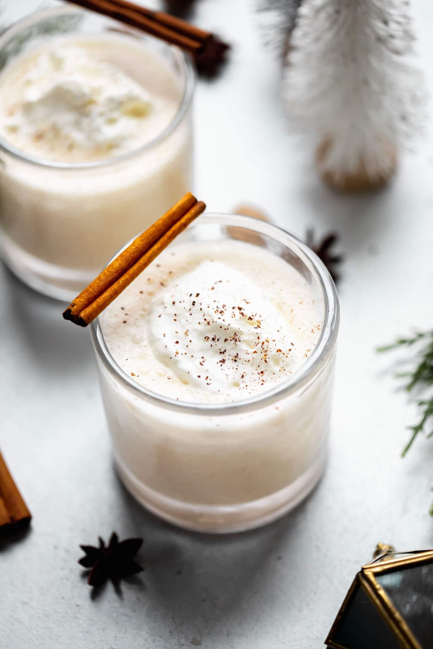 Two glasses of eggnog topped with whipped cream and sprinkle of nutmeg. Garnished with cinnamon stick.