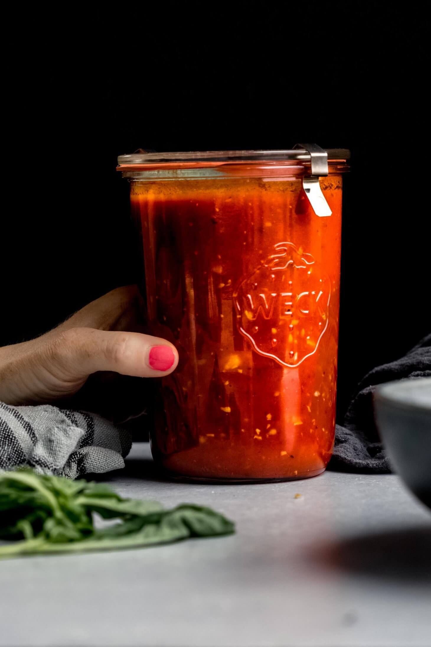 Hand holding jar of homemade marinara sauce.