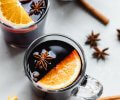 Three mugs of mulled wine on counter next to cinnamon sticks and orange slices.