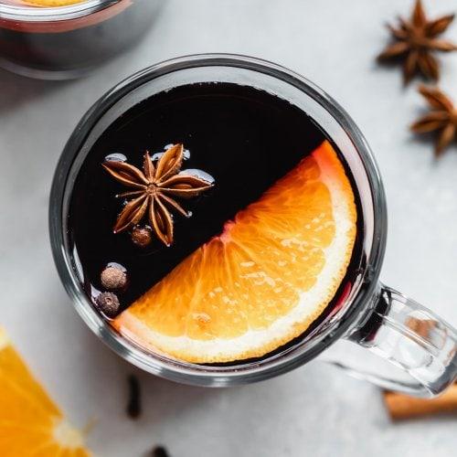 Mug of mulled wine garnished with star anise and orange slice.